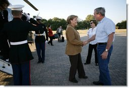 President George W. Bush and Mrs. Laura Bush welcome German Chancellor Angela Merkel and her husband Dr. Joachim Sauer as they arrive via helicopter to the Bush ranch in Crawford, Texas, Friday, Nov. 9, 2007. White House photo by Eric Draper