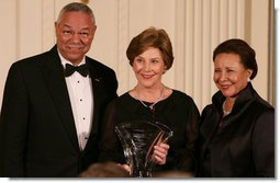 Mrs. Laura Bush is joined on stage by former Secretary of State Colin Powell and his wife, Alma Powell, as they present Mrs. Bush with a National Promise of America Founders Award, Tuesday evening, Nov. 13, 2007, during a social dinner to celebrate the tenth anniversary of America's Promise-The Alliance for Youth. White House photo by Joyce N. Boghosian
