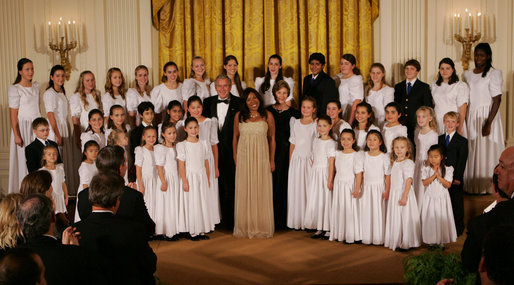 President George W. Bush and Mrs. Laura Bush join singer Melinda Doolittle, center, and members of the World Children's Choir on stage Tuesday evening, Nov. 13, 2007 in the East Room of the White House, during the social dinner in honor of the tenth anniversary of America's Promise-The Alliance for Youth. White House photo by Joyce N. Boghosian