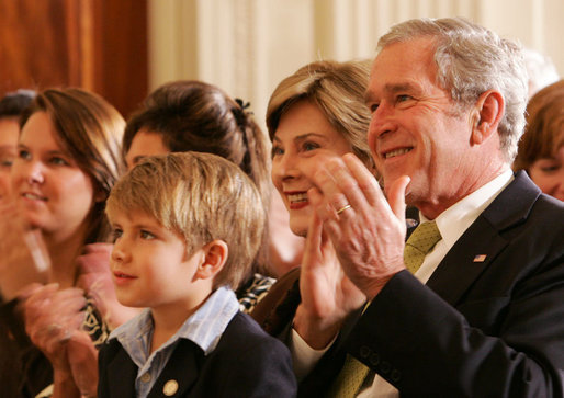 President George W. Bush and Mrs. Laura Bush are joined by Elijah Atkins, Friday, Nov. 16, 2007 in the East Room of the White House, as they listen to Atkins' father, country music star Rodney Atkins, performing for guests during the celebration of National Adoption Day. Rodney Atkins is the 2007-2008 national celebrity spokesperson for The National Council for Adoption. White House photo by Chris Greenberg
