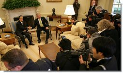 President George W. Bush and Prime Minister Yasuo Fukuda pause for White House press photographers Friday, Nov. 16, 2007, during their meeting in the Oval Office.  White House photo by Eric Draper