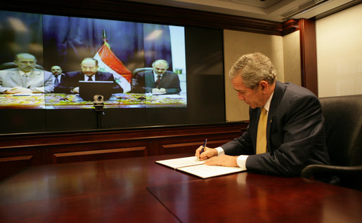President George W. Bush is joined by Iraq's Prime Minister Nouri al-Maliki, center, via video teleconference Monday, Nov. 26, 2007, in signing the U.S.-Iraq Declaration of Principles for Friendship and Cooperation. The declaration is a shared statement of intent that establishes common principles to frame the future relationship between the two countries. White House photo by Eric Draper