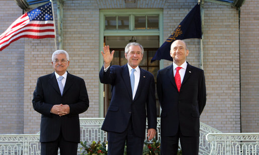 President George W. Bush waves to photographers as he stands with Palestinian President Mahmoud Abbas, left, and Prime Minister Ehud Olmert Tuesday, Nov. 27, 2007, at the Annapolis Conference in Annapolis, Maryland. White House photo by Chris Greenberg