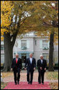 President George W. Bush is flanked by Prime Minister Ehud Olmert, left, of Israel, and President Mahmoud Abbas of the Palestinian Authority as they walk Tuesday, Nov. 27, 2007, from the Buchanan House on the grounds of the U.S. Naval Academy in Annapolis, Maryland, to Bancroft Hall during the Annapolis Conference. The leaders agreed to immediately resume Mideast peace talks. White House photo by Chris Greenberg