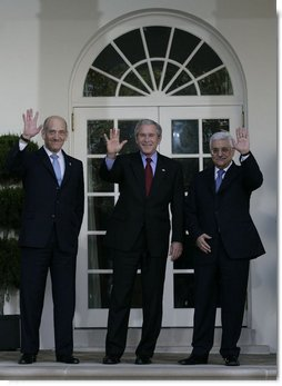 President George W. Bush is flanked by Prime Minister Ehud Olmert, left, of Israel, and President Mahmoud Abbas of the Palestinian Authority, as they wave for the cameras Wednesday, Nov. 28, 2007, after a statement in the Rose Garden regarding the Annapolis Conference.  White House photo by Eric Draper