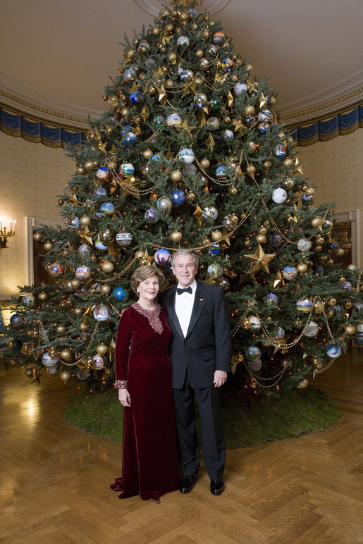 Celebrating the 2007 holiday season, President George W. Bush and Mrs. Laura Bush pose in front of the Christmas Tree in the Blue Room of the White House. White House photo by Eric Draper