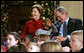 President George W. Bush and Mrs. Laura Bush share a moment with Malik Lawson during the Children's Holiday Performance Monday, Dec. 3, 2007, at the White House. The 7-year-old is the son of Sgt. Sherry Martin, currently serving in Iraq. White House photo by Joyce N. Boghosian