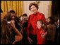 "Mrs. Laura Bush poses for a photo with a young guest following the performance of the Ford's Theater cast members presentation of ""A Christmas Carol,"" Monday, Dec. 3, 2007, at the White House Children's Holiday Reception. White House photo by Shealah Craighead"