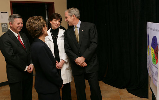 President George W. Bush shares a moment with Nebraska Gov. Dave Heineman, Andrea Skolkin and Kristine McVea, in lab coat, before his tour Wednesday, Dec. 5, 2007, of the OneWorld Community Health Centers Inc. in Omaha. White House photo by Chris Greenberg