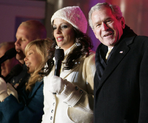 "President George W. Bush joins Sara Evans in singing ""We Wish you a Merry Christmas"" on stage at the Ellipse Thursday, Dec. 6, 2007, during the festivities surround the lighting of the National Christmas Tree. White House photo by Shealah Craighead"