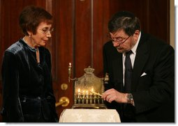 "A Menorah belonging to the great-grandfather of Daniel Pearl is lit by Judea and Ruth Pearl, his parents, during festivities Monday, Dec. 10, 2007, in the Grand Foyer of the White House. Said the President of the slain journalist, ""His only crime was being a Jewish American -- something Daniel Pearl would never deny. Daniel's memory remains close to our hearts. By honoring Daniel, we are given the opportunity to bring forth hope from the darkness of tragedy-- and that is a miracle worth celebrating during the Festival of Lights."" White House photo by Joyce N. Boghosian"