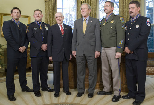 President Bush and U.S. Attorney General Michael Mukasey pose for photos with recipients of the Public Safety Officer Medal of Valor Wednesday, Dec. 12, 2007, in the Oval Office. From left are: Officer Kevin Howland of Sacramento; Officer Todd Myers of West Hartford, Conn.; Attorney General Mukasey; President Bush, Sgt. Kirk Van Orsdel of Hemet, Calif., and David Loving, a firefighter from Richmond, Va. White House photo by Chris Greenberg