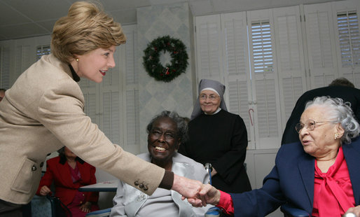 Mrs. Laura Bush reaches out for the hand of a resident of the Little Sisters of the Poor during a visit Tuesday, Dec. 18, 2007, with President George W. Bush to the Washington, D.C. facility that provides nursing and assisted living services to elderly people of lesser means. White House photo by Chris Greenberg