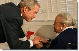 President George W. Bush speaks to a resident at the Little Sisters of the Poor of Washington, D.C., Tuesday, Dec. 18, 2007, during a visit with Mrs. Laura Bush to the facility that provides nursing and assisted-living services to elderly people of lesser means. White House photo by Shealah Craighead