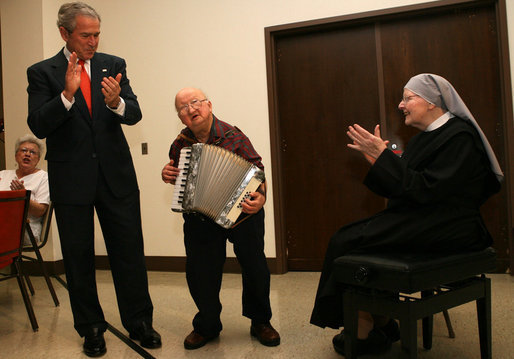 "President George W. Bush and Sister Therese Noel join the festivities as they listen to 75-year-old resident Joe Dignazio of West Virginia, play ""The Eyes of Texas"" during a visit Tuesday, Dec. 18, 2007, to the Washington, D.C. facility. The President told Mr. Dignazio, ""You are really good! Keep playing!"" White House photo by Shealah Craighead"