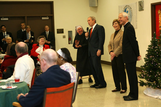 President George W. Bush draws smiles from the audience of volunteers, staff and residents at the Little Sisters of the Poor Tuesday, Dec. 18, 2007, during a visit with Mrs. Laura Bush to the Washington, D.C. facility. Enjoying the moment with them are Mother Benedict de la Passion, Superior and President of Little Sisters of the Poor, and Archbishop Donald Wuerl of the Archdiocese of Washington. White House photo by Shealah Craighead
