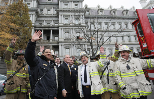 President George W. Bush joins firefighters from the District of Columbia as they wave to the media Wednesday after fighting a fire in the Eisenhower Executive Office Building on the White House complex. The charred, second-floor window frame can be seen in the upper middle of the photo. White House photo by Eric Draper