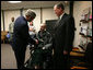 President George W. Bush presents the Purple Heart to U.S. Army Spc. John C. Hoxie of Philippi, W.Va., during a visit Thursday, Dec. 20, 2007, to Walter Reed Army Medical Center in Washington, D.C., where the soldier is recovering from injuries suffered in Operation Iraqi Freedom. Looking on is the soldier's father, David Hoxie. White House photo by Joyce N. Boghosian
