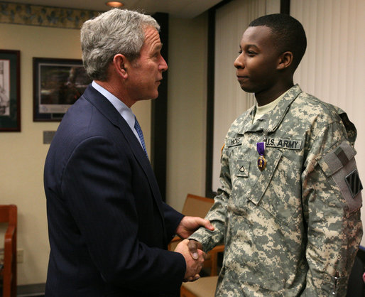 President George W. Bush shakes the hand of U.S. Army PFC Demario Hicks of Fort Stewart, Ga., Thursday, Dec. 20, 2007, after presenting him with a Purple Heart during his visit to Walter Reed Army Medical Center in Washington, D.C., where the soldier is recovering from injuries suffered in Operation Iraqi Freedom. White House photo by Joyce N. Boghosian
