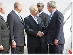 President George W. Bush is greeted by Israel's President Shimon Peres, center, and Prime Minister Ehud Olmert after arriving in Tel Aviv Wednesday, Jan. 9, 2008, for a weeklong visit to the Mideast.  White House photo by Eric Draper