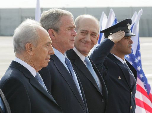 President George W. Bush elicits a smile from Israel's Prime Minister Ehud Olmert, right, as they join Israeli President Shimon Peres for arrival ceremonies Wednesday, Jan. 9, 2008, at Ben Gurion International Airport in Tel Aviv. White House photo by Eric Draper