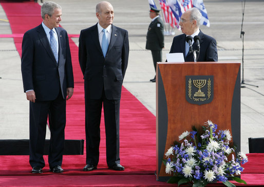 Israel's President Shimon Peres speaks to President George W. Bush during remarks Wednesday, Jan. 9, 2008, at ceremonies welcoming him to Israel. With them is Israeli Prime Minister Ehud Olmert, center. White House photo by Chris Greenberg