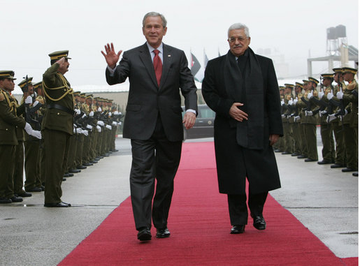 President George W. Bush waves as he and President Mahmoud Abbas of the Palestinian Authority walk the red carpet after the arrival Thursday, Jan. 10, 2008, of President Bush to Ramallah. White House photo by Chris Greenberg