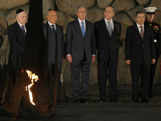 President George W. Bush pauses to pay respects in the Hall of Remembrance Friday, Jan. 11, 2008, at Yad Vashem, the Holocaust Museum in Jerusalem. With him, from left, are: Josef Lapid, Chairman of the Yad Vashem Council; Israel's President Shimon Peres, Israel's Prime Minister Ehud Olmert, and Avner Shalev, Chairman of the Yad Vashem Directorate. White House photo by Eric Draper