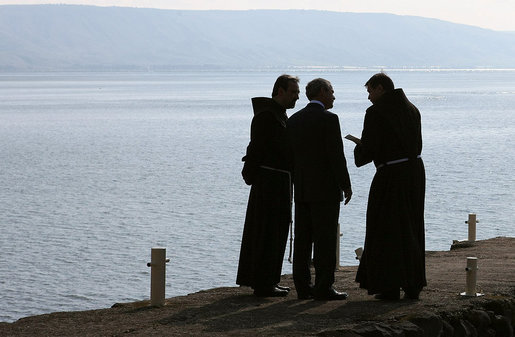 President George W. Bush is accompanied by two friars as he views the Sea of Galilee Friday, Jan. 11, 2008, during his visit to Capernaum before leaving Israel. According to sources, the location was that where Jesus walked upon the water. White House photo by Eric Draper