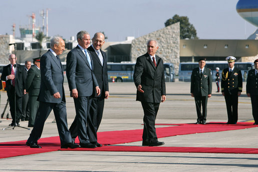 President George W. Bush is flanked by Israel's President Shimon Peres, left, and Prime Minister Ehud Olmert as they arrive at Tel Aviv's Ben Gurion International Airport Friday, Jan. 11, 2008, prior to the departure of Air Force One. White House photo by Chris Greenberg