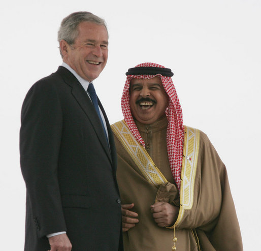 President George W. Bush smiles as he stands with King Hamad Bin Isa Al-Khalifa as they view the honor guard Saturday, Jan. 12, 2008, during arrival ceremonies in Manama, Bahrain. White House photo by Chris Greenberg