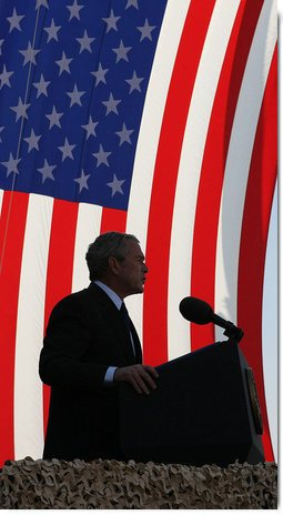 "President George W. Bush stands in front of a U.S. flag Saturday, Jan. 12, 2008, as he addresses military personnel and coalition forces at Camp Arifjan in Kuwait. The President told the troops, ""It's hard work you're doing, but it's necessary work."" White House photo by Eric Draper"