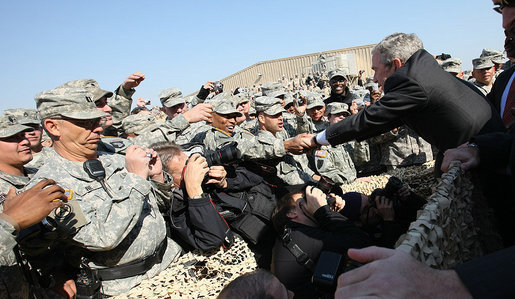 Troops reach out for President George W. Bush as he leaves the stage after delivering remarks to military personnel and coalition forces at Camp Arifjan before departing Kuwait Saturday, Jan. 12, 2008, for Bahrain. White House photo by Eric Draper