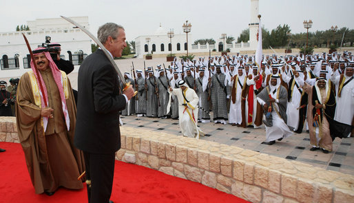 President George W. Bush enjoys the moment with performers Saturday, Jan. 12, 2008, after being presented with a sword by King Hamad Bin Isa Al-Khalifa, left, during arrival ceremonies in Manama, Bahrain. White House photo by Eric Draper