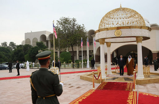 President George W. Bush and President Sheikh Khalifa bin Zayed Al Nahyan of the United Arab Emirates, stand for their national anthems Sunday, Jan. 13, 2008, during arrival ceremonies for President Bush in the courtyard of Al Mushref Palace in Abu Dhabi. White House photo by Eric Draper