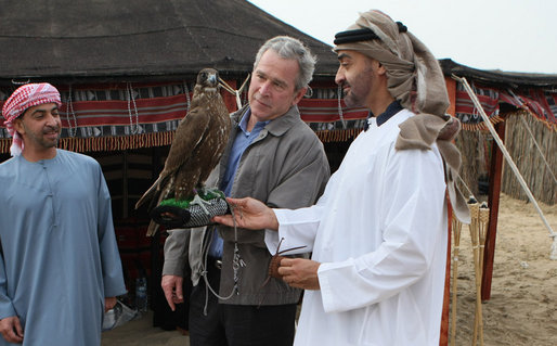 President George W. Bush holds a falcon as the Crown Prince of Abu Dhabi, Sheikh Mohammed bin Zayed Al Nayhan, stands by during dinner Sunday night, Jan. 13, 2008 in the desert near Abu Dhabi. White House photo by Eric Draper