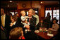 President George W. Bush gets up close and personal with a child as he arrived Friday, Feb. 1, 2008, at Eggtc., a home-style restaurant in Kansas City, where he met local business leaders over breakfast. White House photo by Eric Draper