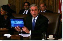 "President George W. Bush holds up a computer with the E-Budget for the cameras during a Cabinet meeting Monday, Feb. 4, 2008. Later, the President said, ""I submitted the budget today to Congress -- it's on a laptop notebook, an e-budget. It saves paper, saves trees, saves money. I think it's the first budget submitted electronically. And it's a good budget. It's a budget that achieves some important objectives. One, it understands our top priority is to defend our country, so we fund our military, as well as fund the homeland security. Secondly, the budget keeps our economy growing."" White House photo by Joyce N. Boghosian"