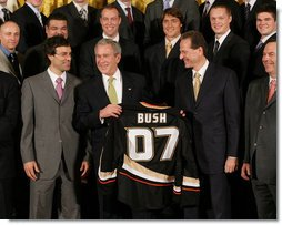 President George W. Bush stands between Scotty Niedermayer, left, and Ducks' owner Henry Samueli as he holds up a BUSH 07 Anaheim Ducks jersey Wednesday, Feb. 6, 2008, after welcoming the 2007 Stanley Cup champions to the East Room of the White House. White House photo by Eric Draper