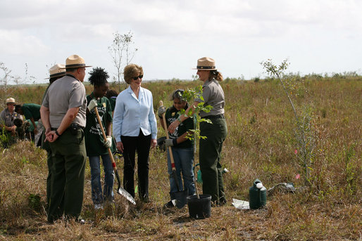 "Mrs. Laura Bush joins Florida City Elementary School students Cornesha Dericho, left, and Dania Amaya, along with park ranger Allyson Gantt, right, as they prepare to plant a Gumbo Limbo tree Wednesday, Feb. 6, 2008, during the Junior Ranger ""First Bloom"" planting event in Everglades National Park, Fla. Mrs. Bush praised the Everglades restoration program which hopes to plant native trees to replace invasive species that are choking the park. White House photo by Shealah Craighead"