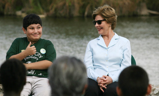 "Mrs. Laura Bush smiles as a Florida City Elementary School student gives a thumbs-up while sitting on stage with Mrs. Bush, Wednesday, Feb. 6, 2008, during the Junior Ranger ""First Bloom"" planting event in Everglades National Park, Fla. Mrs. Bush praised the Everglades restoration program which will help bring back native trees in areas of the Everglades overgrown with non-native plants. White House photo by Shealah Craighead"