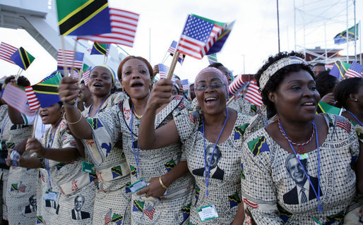 Tanzanian women in dresses bearing the likeness of President George W. Bush wave flags from Tanzania and the United States as they await the arrival Saturday, Feb. 16, 2008, at Julius Nyerere International Airport in Dar es Salaam of President Bush and Mrs. Laura Bush. White House photo by Chris Greenberg