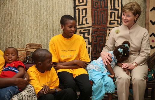 A young girl rests her head on Mrs. Laura Bush's lap Sunday, Feb. 17, 2008, as she visits with orphans and caretakers in the Living Room of the WAMA Foundation, a non-profit organization founded by Salma Kikwete, First Lady of Tanzania. White House photo by Shealah Craighead