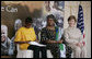 Mrs. Laura Bush and Mrs. Salma Kikwete, First Lady of Tanzania, enjoy Salvation Army Children as they perform on stage Sunday, Feb. 17, 2008, at the WAMA Foundation in Dar es Salaam. The foundation, founded by Mrs. Kikwete, is a non-profit organization focusing on development by improving women's social and economic status by redefining gender roles and creating more opportunities for the development of women and children. White House photo by Shealah Craighead