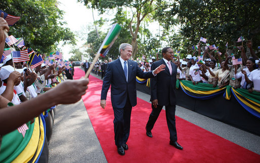 President George W. Bush and President Jakaya Kikwete of Tanzania acknowledge the crowd as they walk through the ceremonial arrival cordon Sunday, Feb. 17, 2008, at the State House in Dar es Salaam. White House photo by Eric Draper