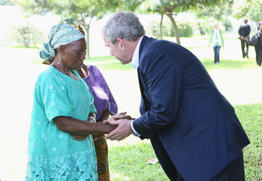 President George W. Bush meets with a family member Sunday, Feb. 17, 2008 at the memorial garden of the U.S. Embassy in Dar es Salaam in Tanzania, during a memorial remembrance for those who died in the 1998 U.S. Embassy bombing. White House photo by Eric Draper