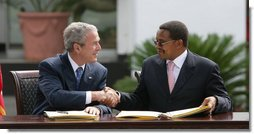 "President George W. Bush and President Jakaya Kikwete of Tanzania, shake hands after signing the $698 million Millennium Challenge Compact Sunday, Feb. 17, 2008, in Dar es Salaam. In signing the compact, President Bush said, ""We are partners in democracy. We believe that governments ought to respond to the people. We're also partners in fighting disease, extending opportunity and working for peace. Mr. President, I mentioned I was proud to sign, along with the President, the largest Millennium Challenge Account in the history of the United States here in Tanzania. It will provide nearly $700 million over five years to improve Tanzania's transportation network, secure reliable supplies of energy, and expand access to clean and safe water. White House photo by Chris Greenberg"