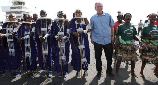 President George W. Bush is welcomed by Maasai dancers on his arrival Monday, Feb. 18, 2008 to the airport in Arusha, Tanzania. White House photo by Eric Draper