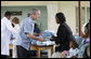 President George W. Bush presents a mosquito net to a patient during a tour Monday, Feb. 18, 2008, of the Meru District Hospital outpatient clinic in Arusha, Tanzania. The mosquito nets are part of a program to help in the battle against malaria. White House photo by Eric Draper
