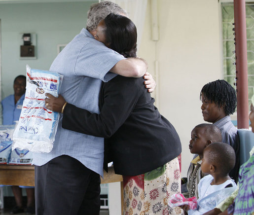 President George W. Bush embraces a pregnant woman after presenting her with a mosquito net during a tour Monday, Feb. 18, 2008, of the Meru District Hospital outpatient clinic in Arusha, Tanzania. The presentation of mosquito nets is part of a program to help in the battle against malaria. White House photo by Eric Draper